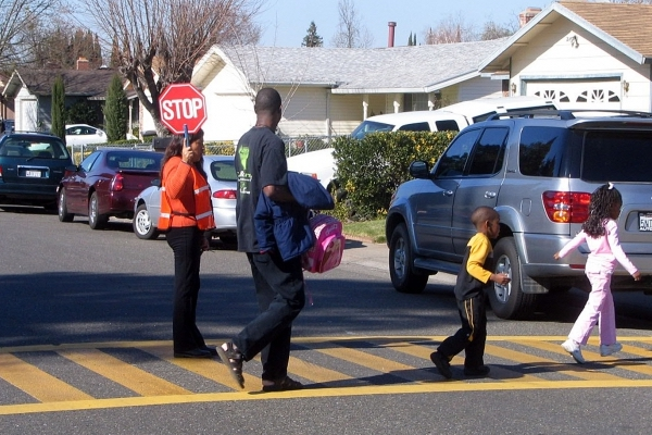 Children crossing the street with crossing guard
